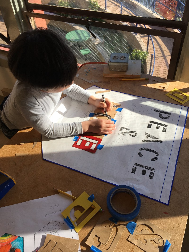 Tiny Artists – Child stenciling text
